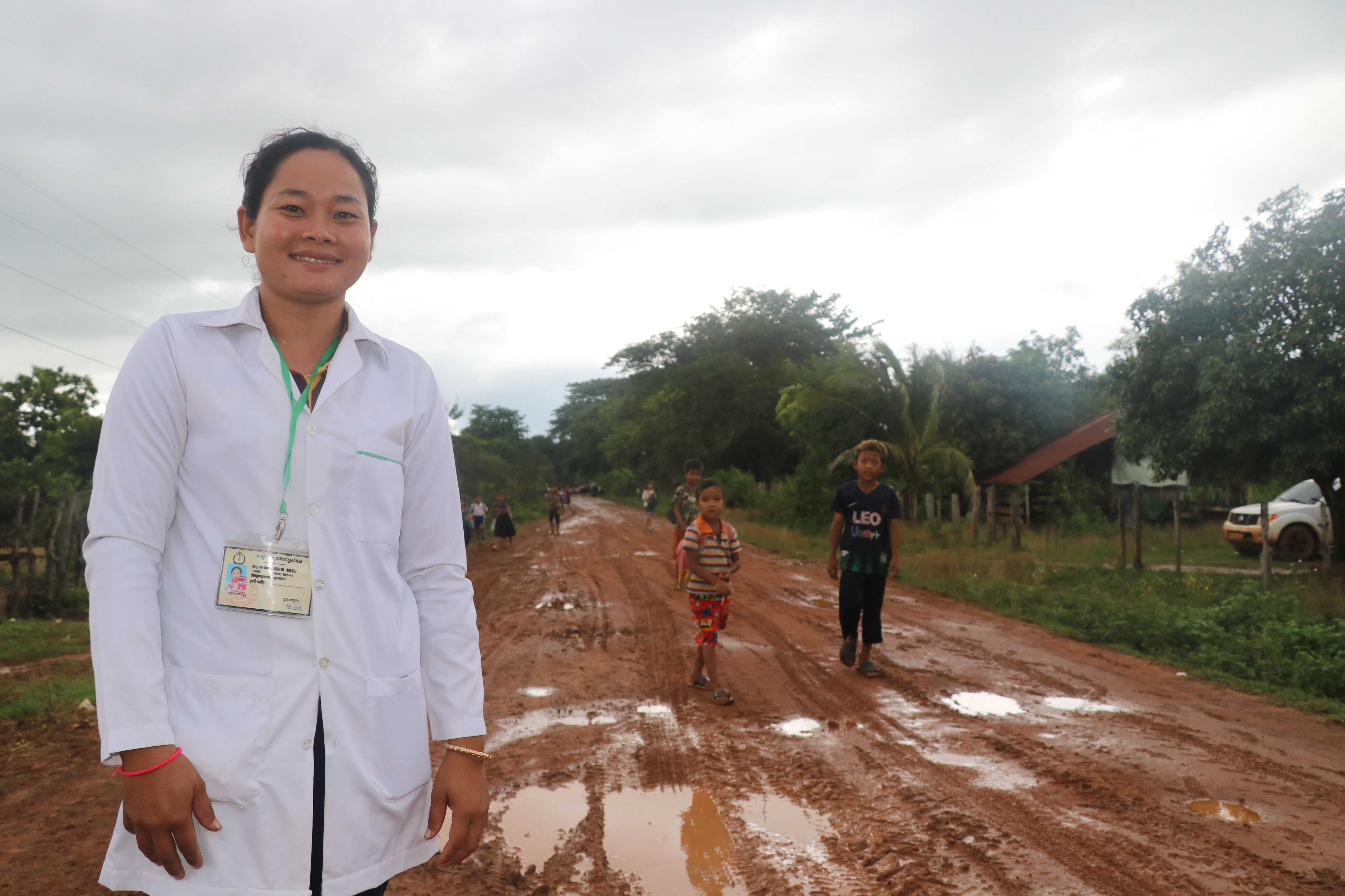 Ratana stands in a dirt-road from the health post to village